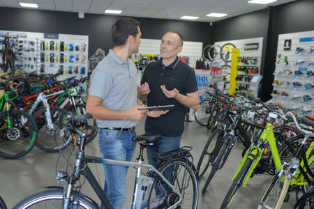 a two wheeled vehicle: Two men in discussion in bicycle shop Stock Photo