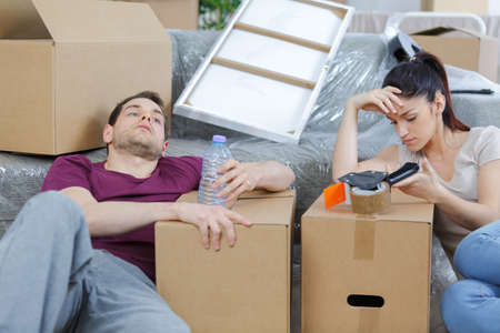 dispense: Exhausted young couple amongst boxes