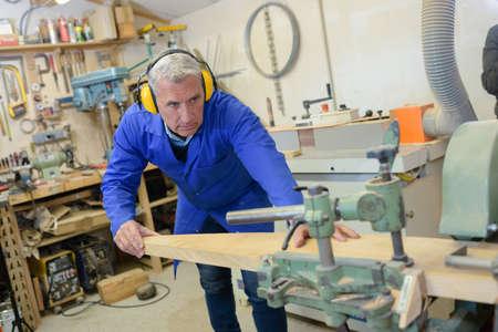Senior houtbewerker met machines