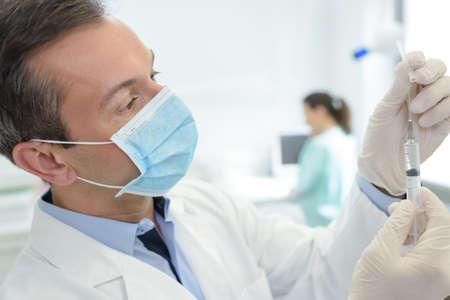 sheath: Masked medical worker preparaing syringe