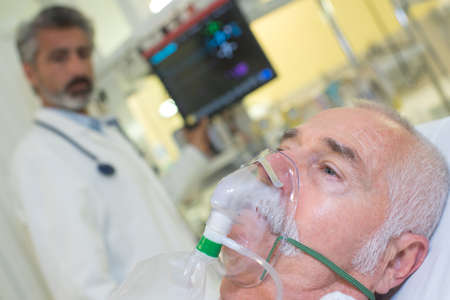 Doctor looking at patient wearing oxygen mask