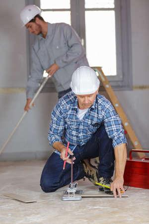 Workman using tile cutter
