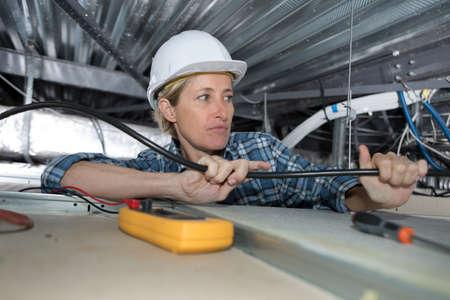 좁은 공간에서 일하는 여성 전기 기사