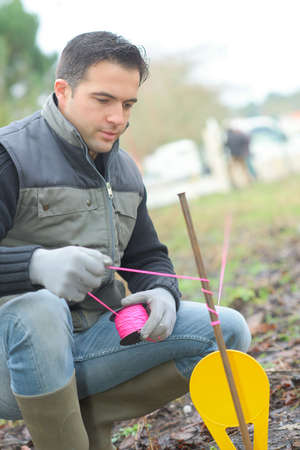 Man marking boundary with string Stock Photo