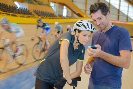 Coach showing timer to cyclist Stock Photo
