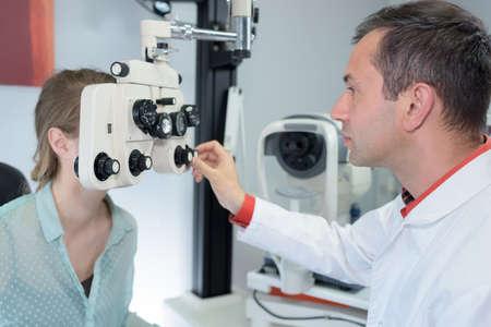 Optometrist adjusting equipment during consultation