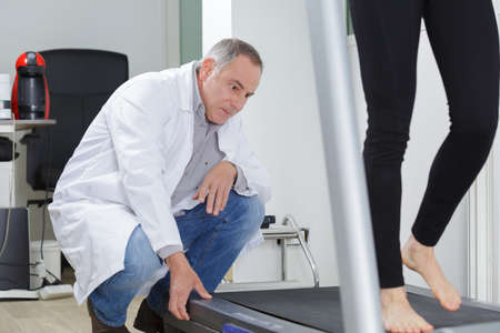 Specialist watching woman walk on tread mill Stockfoto