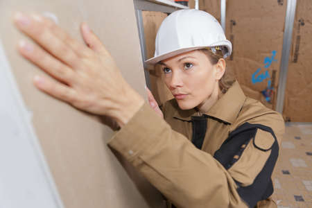 handywoman: young female builder working indoors Stock Photo