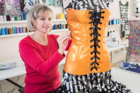 Dressmaker altering bodice on mannequin
