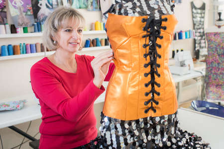 designate: Dressmaker altering bodice on mannequin