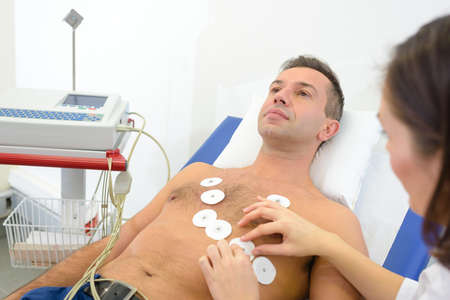 Nurse attaching heart monitor pads to mans chest Stock Photo