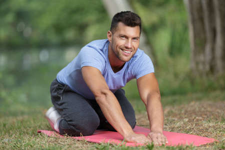 Portrait of man exercising on mat outdoors Stock Photo