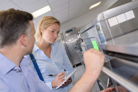Woman inspecting kitchen, making notes Foto de archivo