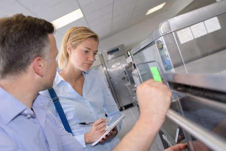 Vrouw die keuken inspecteert, notities maken Stockfoto