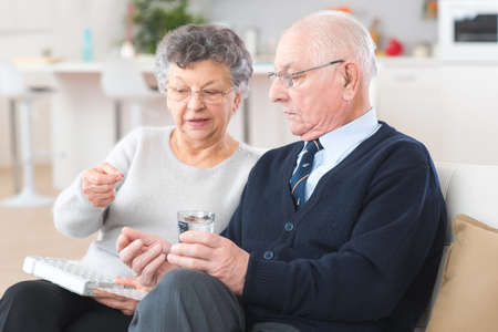 Elderly woman administering medication to husband from pillbox Stock Photo