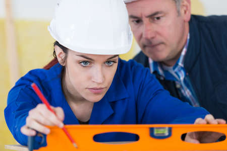 Manager overseeing young lady using spirit level
