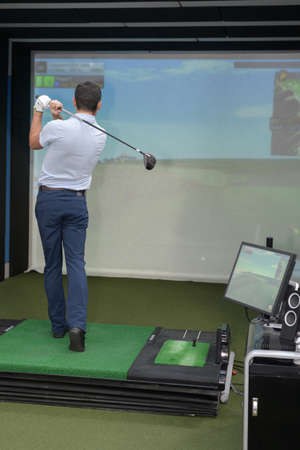 Man practicing golf on indoor simulator Stok Fotoğraf
