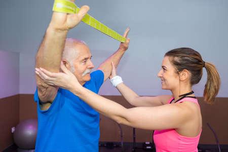 fisioterapeuta que trabaja con el hombre mayor que usa la correa