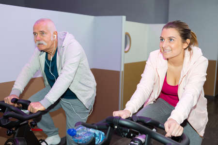 senior man and young lady on static cycle machines Stock fotó