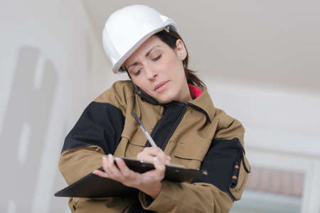 designate: female contractor holding clipboard and talking on the phone Stock Photo