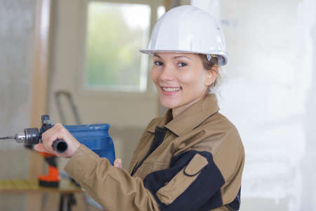 handywoman: happy female contractor drilling a wall in a construction site