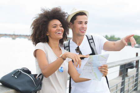 couple tourists with map near river in a city