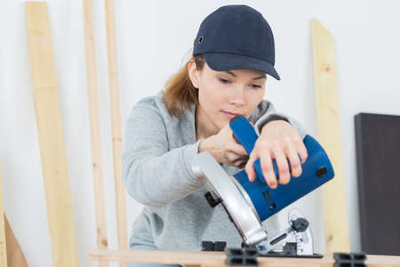 workroom: female carpenter using electric sander