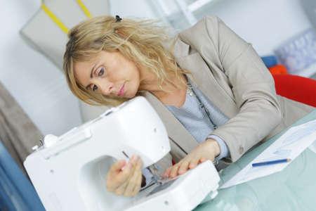 needlewoman: a female dressmaker sewing cloth Stock Photo