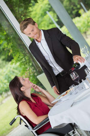 disabled woman sitting in restaurant - waiter pouring red wine Stock Photo