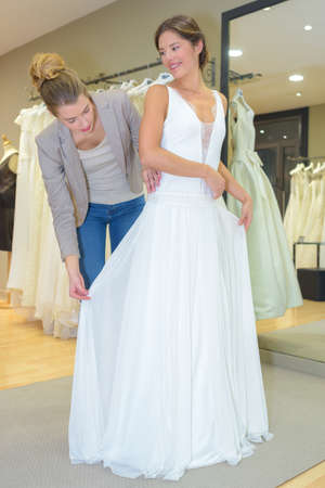 female trying on wedding dress in a shop with assistant