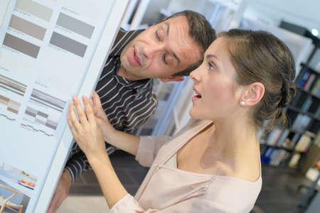 designate: male interior decorator advising customer on paint colours