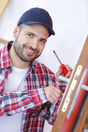attractive young builder is installing doorlock