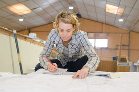 young woman looking at blueprints