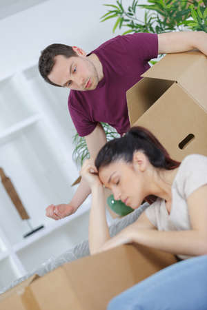 young couple moving husband angry at exhausted wife