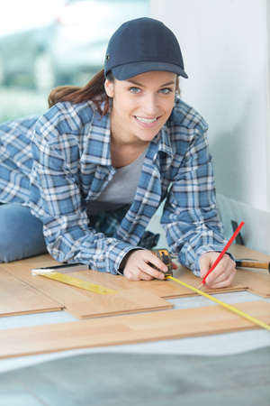 furniture part: woman assembling furniture at home on the floor