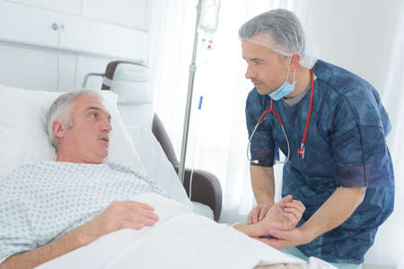 friendly male doctor hold patient hand in hospital room Stock Photo