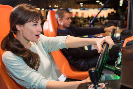 hitech: a young couple in casual clothes playing racing game
