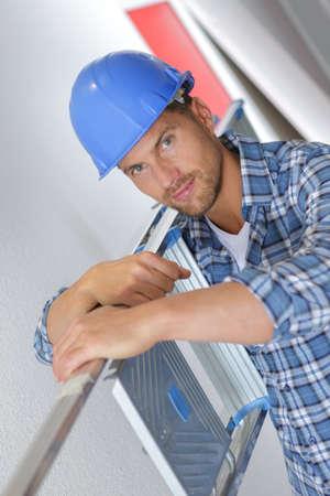Portrait of construction worker carrying ladder on shoulder