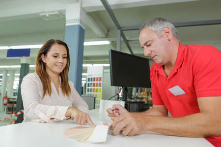 printout: man and woman discussing new paint colors at hardware store Stock Photo