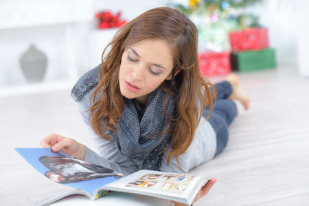 attractive young female lying on wooden floor and reading book