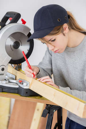 waistup: female carpenter measuring wood with scale in workshop Stock Photo