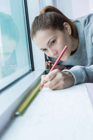 thermoplastic: female worker measuring window glass