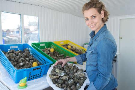 Vrouwelijke oester werknemer bij oesterboerderij of restaurant