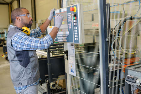 experiencing: male electrician repairing industrial machine control component