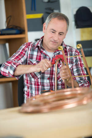 craftswoman: craftman cutting a cooper cable