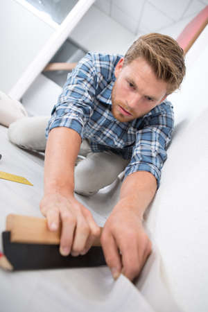 young man fitting carefully a roll of carpet Stock Photo