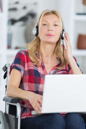 woman using laptop while listening music on wheelchair