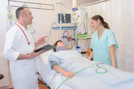 prescribing: doctor and nurse with patient in hospital Stock Photo