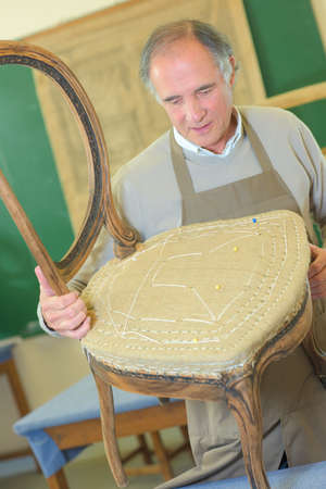 round chairs: man upholstering chair in his workshop Stock Photo