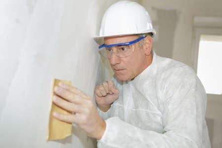 senior man wearing protection sanding interior wall for restoration Stock Photo